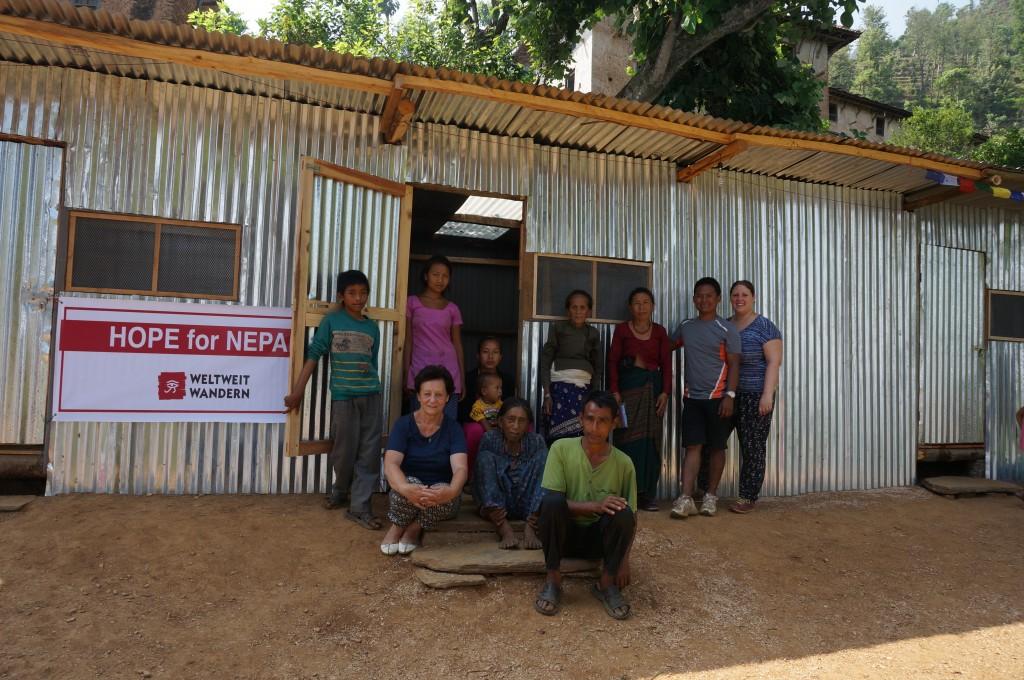 Sandra, Ihre Familie und Team vor einer der neuerrichteten Hütten